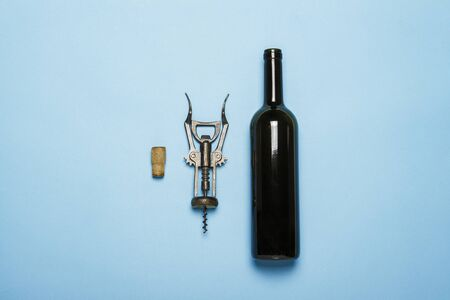 Bottle of wine and corkscrew on a blue background. Concept sommelier, wine tasting, wine accessories. Flat lay, top view.