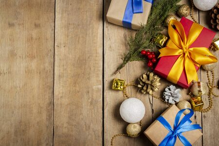 Several gift boxes, Christmas decorations, Christmas tree branch on a wooden background. The concept of Christmas, winter holidays, new year. Flat lay, top view.