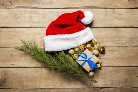 Santa Claus hat, gift, Christmas-tree decorations on a wooden background. The concept of Christmas, winter holidays, new year, postcard. Flat lay, top view. Stok Fotoğraf