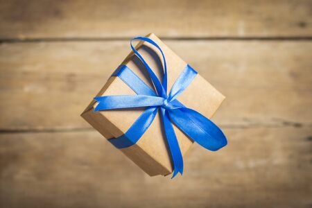 Flying gift box on a wooden background. Holiday concept, christmas. Levitation. Banco de Imagens - 133462337