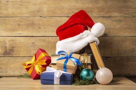 Pile of books, Santa Claus hat, Christmas-tree decorations and Gifts on a wooden background. Holiday concept, christmas, christmas eve. Banco de Imagens - 133462341