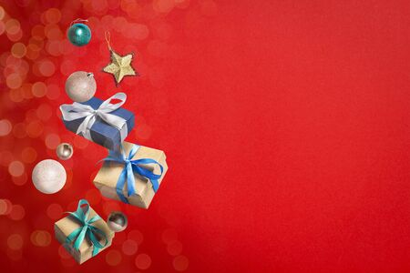 Flying gift boxes and Christmas decorations on a red background. Holiday concept, christmas. Levitation. Items in the air. Flat lay, top view. Banco de Imagens - 133462342