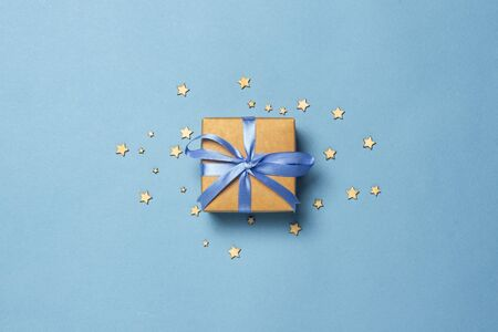 Gift box with blue ribbon on a blue background with decorative stars. Gift concept for a loved one, holiday .Flat lay, top view.