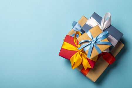 Stack of gifts on a blue background. Gift concept for a loved one, holiday, Christmas. Flat lay, top view. Banco de Imagens - 133462347