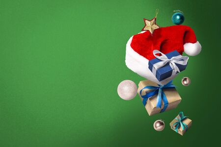 Flying Santa Claus hat, gift box and Christmas decorations on a green background. Holiday concept, christmas. Levitation. Items in the air. Flat lay, top view. Banco de Imagens