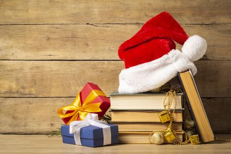 Pile of books, Santa Claus hat, Christmas-tree decorations and Gifts on a wooden background. Holiday concept, christmas, christmas eve.