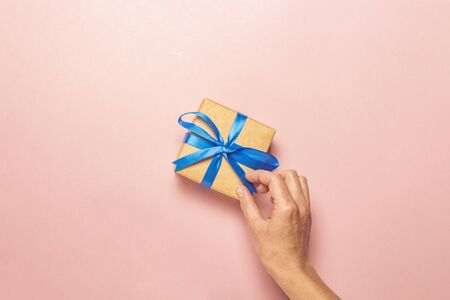 Female hand holds a gift on a pink background. Gift concept for a loved one, holiday, christmas. Flat lay, top view.