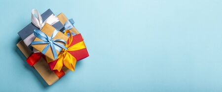 Stack of gifts on a blue background. Gift concept for a loved one, holiday, Christmas. Banner. Flat lay, top view.