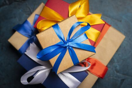 Stack of gift boxes on a dark blue stone background. Holiday concept, christmas, christmas eve. Flat lay, top view. Banco de Imagens