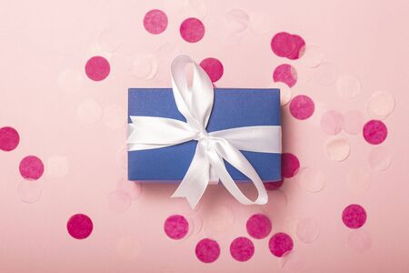 Gift on a pink background with confetti. Gift concept for a loved one, holiday, christmas. Levitation. Flat lay, top view. Banco de Imagens - 133462379