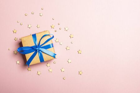 Gift box on a pink background with stars. Gift concept for a loved one, holiday, Christmas. Flat lay, top view.