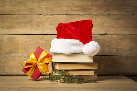Pile of books, Santa Claus hat, Christmas-tree decorations and Gifts on a wooden background. Holiday concept, christmas, christmas eve. Banco de Imagens - 133462401