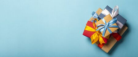Stack of gifts on a blue background. Gift concept for a loved one, holiday, Christmas. Banner. Flat lay, top view. Banco de Imagens - 133462402