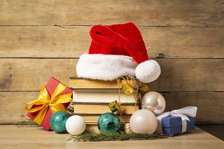 Pile of books, Santa Claus hat, Christmas-tree decorations and Gifts on a wooden background. Holiday concept, christmas, christmas eve. Banco de Imagens - 133462404