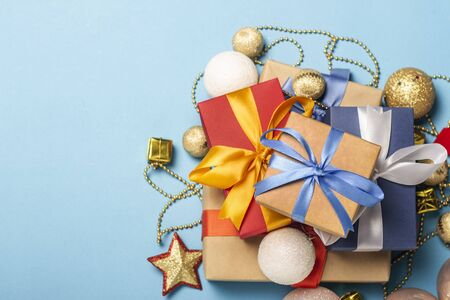 A stack of gifts and Christmas decorations on a blue background. Gift concept for a loved one, holiday, Christmas. Flat lay, top view. Banco de Imagens