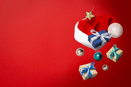 Flying Santa Claus hat, gift box and Christmas decorations on a red background. Holiday concept, christmas. Levitation. Items in the air. Flat lay, top view. Banco de Imagens - 133462419