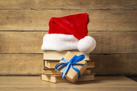 Pile of books, Santa Claus hat and Gift on a wooden background. Holiday concept, christmas, christmas eve. Banco de Imagens
