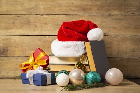 Pile of books, Santa Claus hat, Christmas-tree decorations and Gifts on a wooden background. Holiday concept, christmas, christmas eve. Banco de Imagens - 133462430