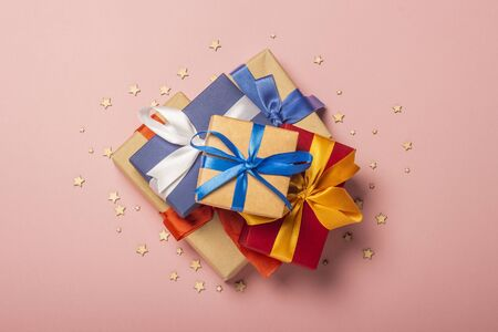 Stack of gifts on a pink background with stars. Gift concept for a loved one, holiday, Christmas. Flat lay, top view. Banco de Imagens - 133462431