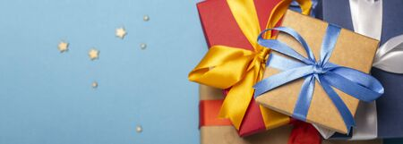 A stack of gifts on a blue background with decorative stars and bokeh. Gift concept for a loved one, holiday. Flat lay, top view. Banco de Imagens - 133462433