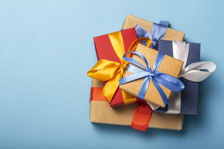 Stack of gifts on a blue background. Gift concept for a loved one, holiday, Christmas. Flat lay, top view. Banco de Imagens - 133462434