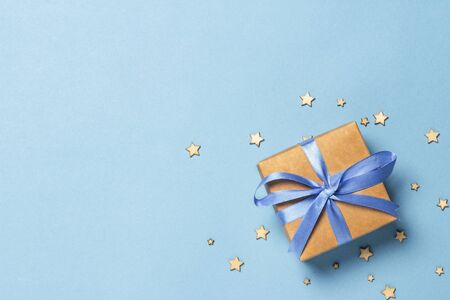 Gift box with blue ribbon on a blue background with decorative stars. Gift concept for a loved one, holiday .Flat lay, top view. Banco de Imagens - 133462435