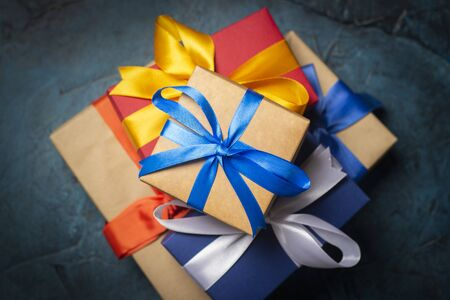Stack of gift boxes on a dark blue stone background. Holiday concept, christmas, christmas eve. Flat lay, top view. Banco de Imagens - 133462436