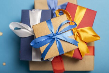 A stack of gifts on a blue background with decorative stars and bokeh. Gift concept for a loved one, holiday. Flat lay, top view. Banco de Imagens - 133462439