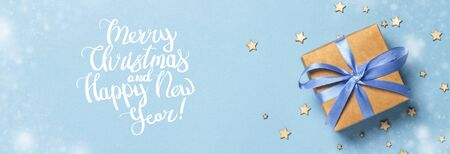 Gift box with blue ribbon on a blue background with decorative stars. Added Merry Christmas text. Gift concept for a loved one, holiday. Banner .Flat lay, top view.