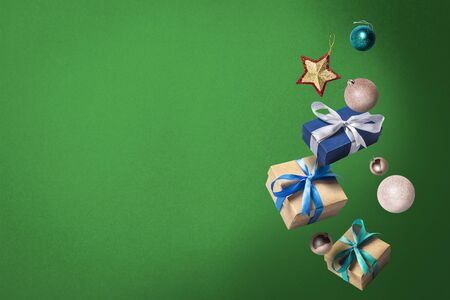 Flying gift boxes and Christmas decorations on a green background. Holiday concept, christmas. Levitation. Items in the air. Flat lay, top view.