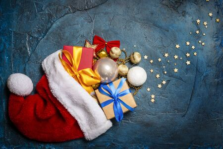 Santa Claus hat, Christmas decorations and Gift boxes on a dark blue stone background. Holiday concept, christmas, christmas eve. Flat lay, top view.