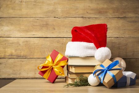 Pile of books, Santa Claus hat, Christmas-tree decorations and Gifts on a wooden background. Holiday concept, christmas, christmas eve. Banco de Imagens - 133462451