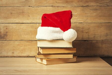 Stack of books, Santa's hat on a wooden background. Holiday concept, christmas, christmas eve.