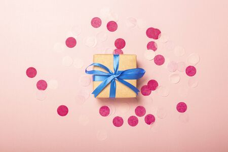 Gift on a pink background with confetti. Gift concept for a loved one, holiday, christmas. Levitation. Flat lay, top view. Banco de Imagens - 133462463