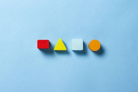Children's educational toys geometric shapes for logic on a blue background. The concept of education, child development, logic and ingenuity. Flat lay, top view.