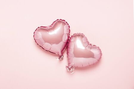 Two pink air balloons in the shape of a heart on a pink background. Concept Valentines Day, Wedding Decoration. Foil balls. Flat lay, top view. Banco de Imagens