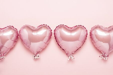 Pink air balloons in the shape of a heart on a pink background. Concept for Valentines day, decoration, wedding, invitation or photo zone. Foil balls. Flat lay, top view.