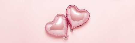 Two pink air balloons in the shape of a heart on a pink background. Concept Valentines Day, Wedding Decoration. Foil balls. Banner. Flat lay, top view.