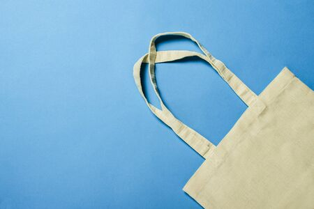 Bright linen bag for shopping on a blue background. Eco material. Shopping concept, place for . Flat lay, top view.