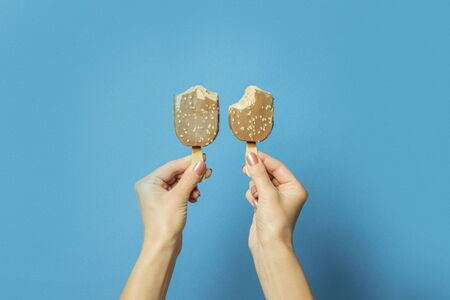 Two hands holds bitten ice cream on a stick on a blue background. Hot summer concept, a pair of lovers, lovers. Flat lay, top view.