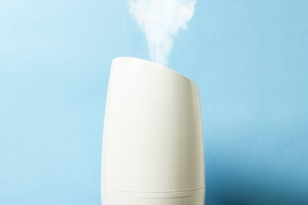 Steam humidifier with steam over a white background. Health care concept, dust control. Side view.