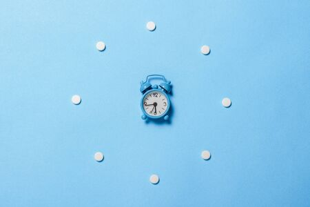 Pills laid out in the form of a round dial and an alarm clock on a blue background. The concept of insomnia, taking pills according to the regimen, vitamins. Flat lay, top view. 免版税图像