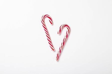 Candy caramel cane on a white background. Concept Christmas, New Year, minimalism. Flat lay, top view.
