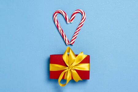 Candy caramel cane in the form of a heart and a gift box on a blue background. Concept Christmas, New Year, minimalism. Banner. Flat lay, top view. Banco de Imagens
