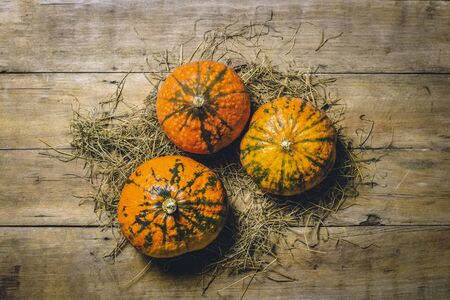 Ripe pumpkins on a wooden background. Harvest concept, autumn, halloween eve. Banner. Flat lay, top view.