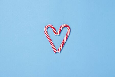 Candy caramel cane in the form of a heart on a blue background. Concept Christmas, New Year, minimalism. Flat lay, top view.