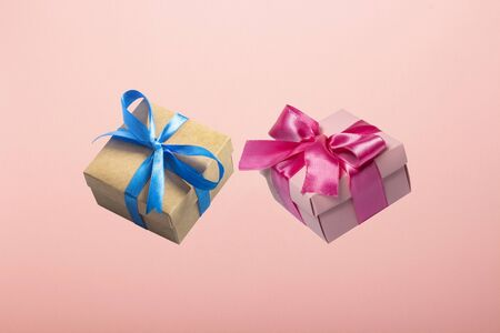 Two gifts flying in the air on a pink background. Concept gift for a loved one, birthday, Valentines Day. Levitation.