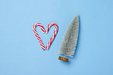 Decorative Christmas tree and candy caramel cane in the form of a heart on a blue background. Concept Christmas, New Year, minimalism. Flat lay, top view.