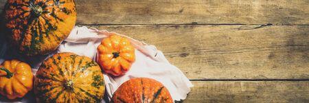 Pumpkins on a wooden background. Harvest concept, autumn, Halloween eve. Banner. Flat lay, top view. Banco de Imagens