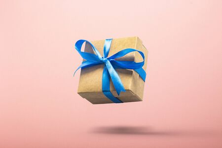 Gift flying in the air on a pink background. Concept gift for a loved one, birthday, Valentines Day. Levitation. Banco de Imagens